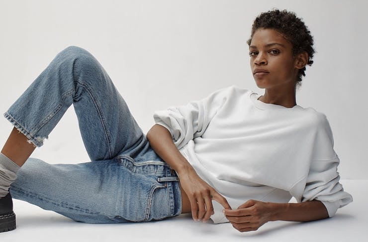 A woman wearing Agolde jeans with a white sweater.