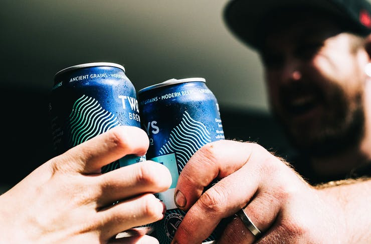 Two people cheers-ing with blue tinnies.