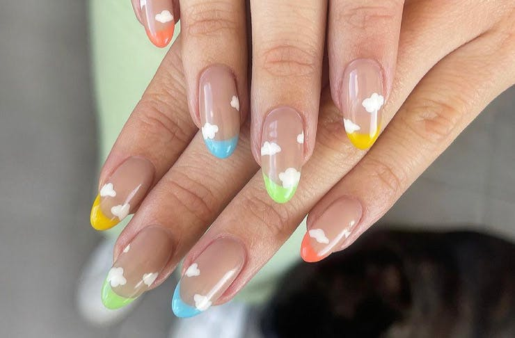 Hands showing nail art featuring blue, green, and yellow tips with soft clouds.
