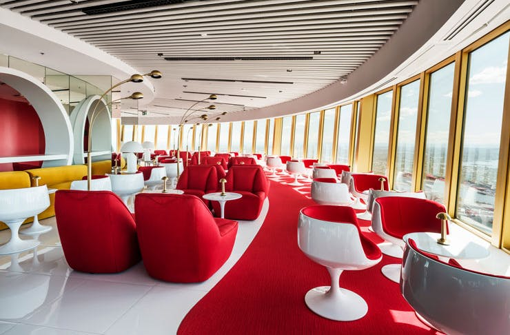 Plush red lounges and 60s-style white lounge chairs at Bar 83 cocktail lounge in Sydney.