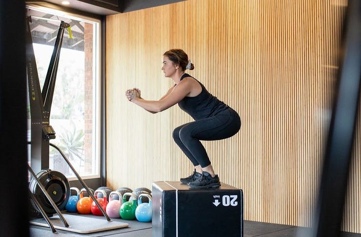 person jumping on box at a boutique gym