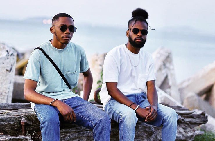 Two men wearing Cotton On t-shirts and jeans at the beach.
