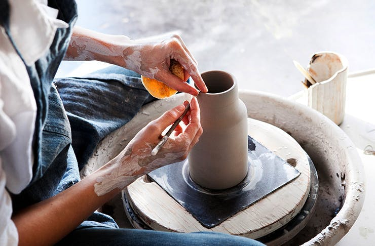Person using pottery spinning wheel to create a vase at one of the best pottery classes in Perth