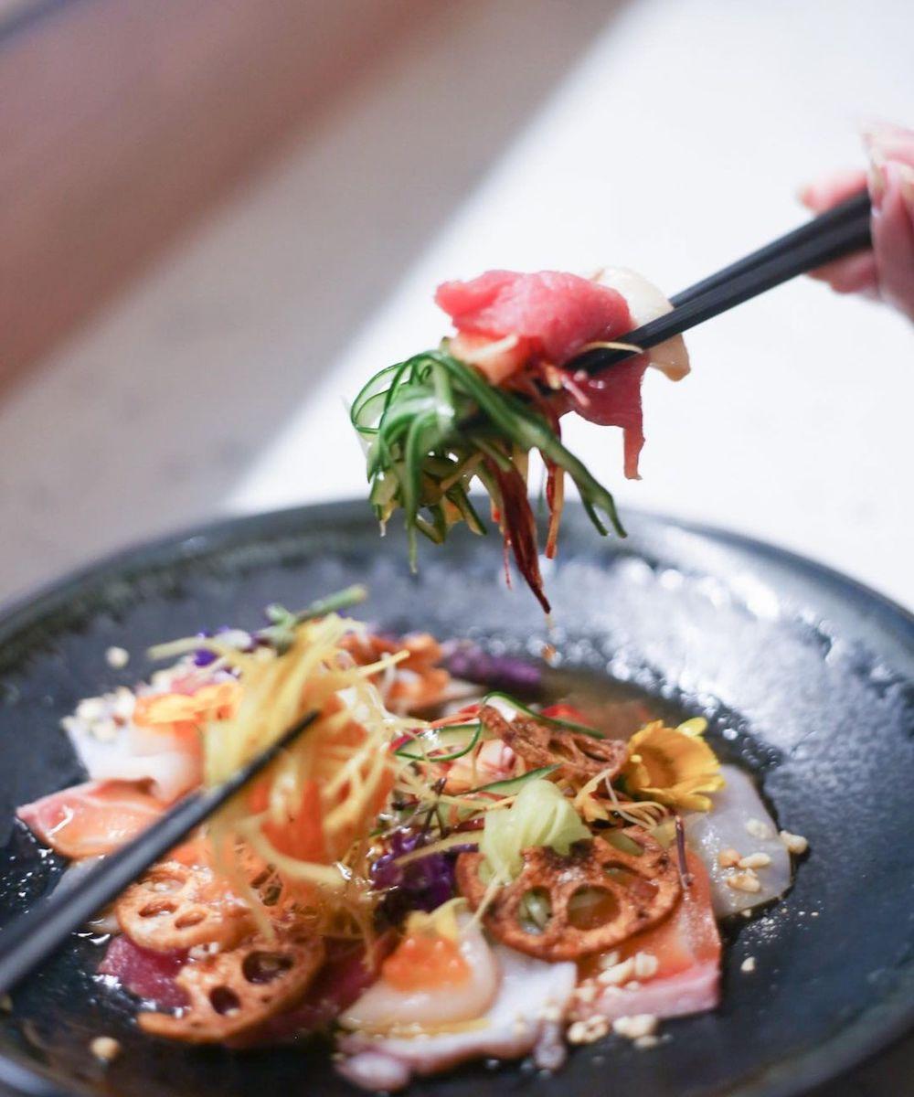 chopsticks dig into delicate sashimi at Yuuma