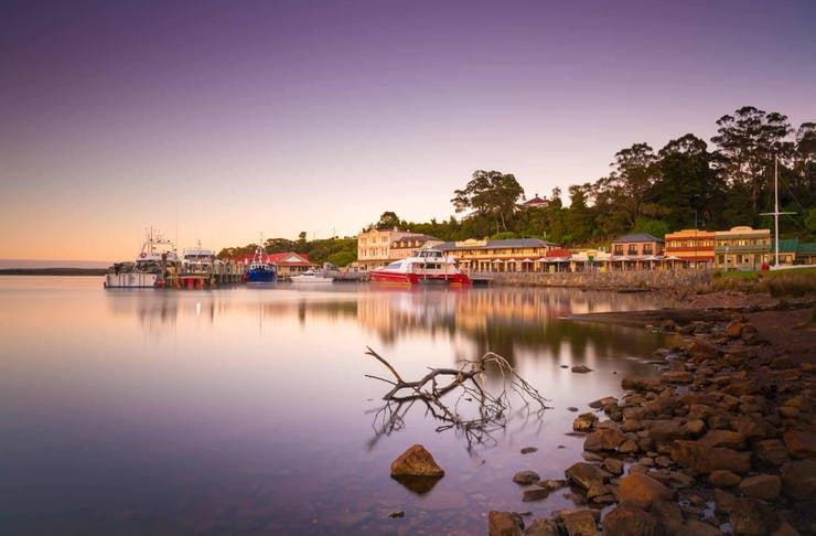 A stunning, purple and pink hued sunset shot of the town of Strahan in Tasmania.