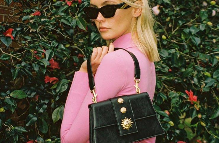 A model holding a black Poppy Lissiman vegan handbag.