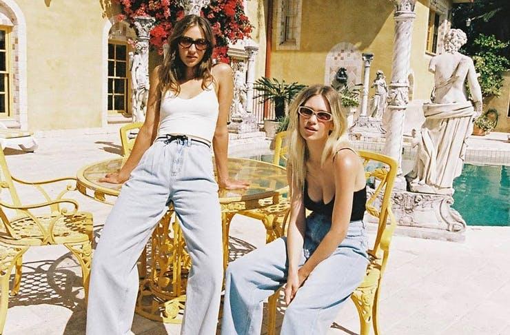 Models sitting by a pool wearing wide leg jeans.