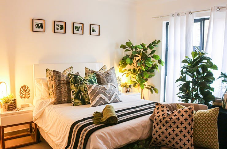 a bed inside a sunlit bedroom with plants by the window