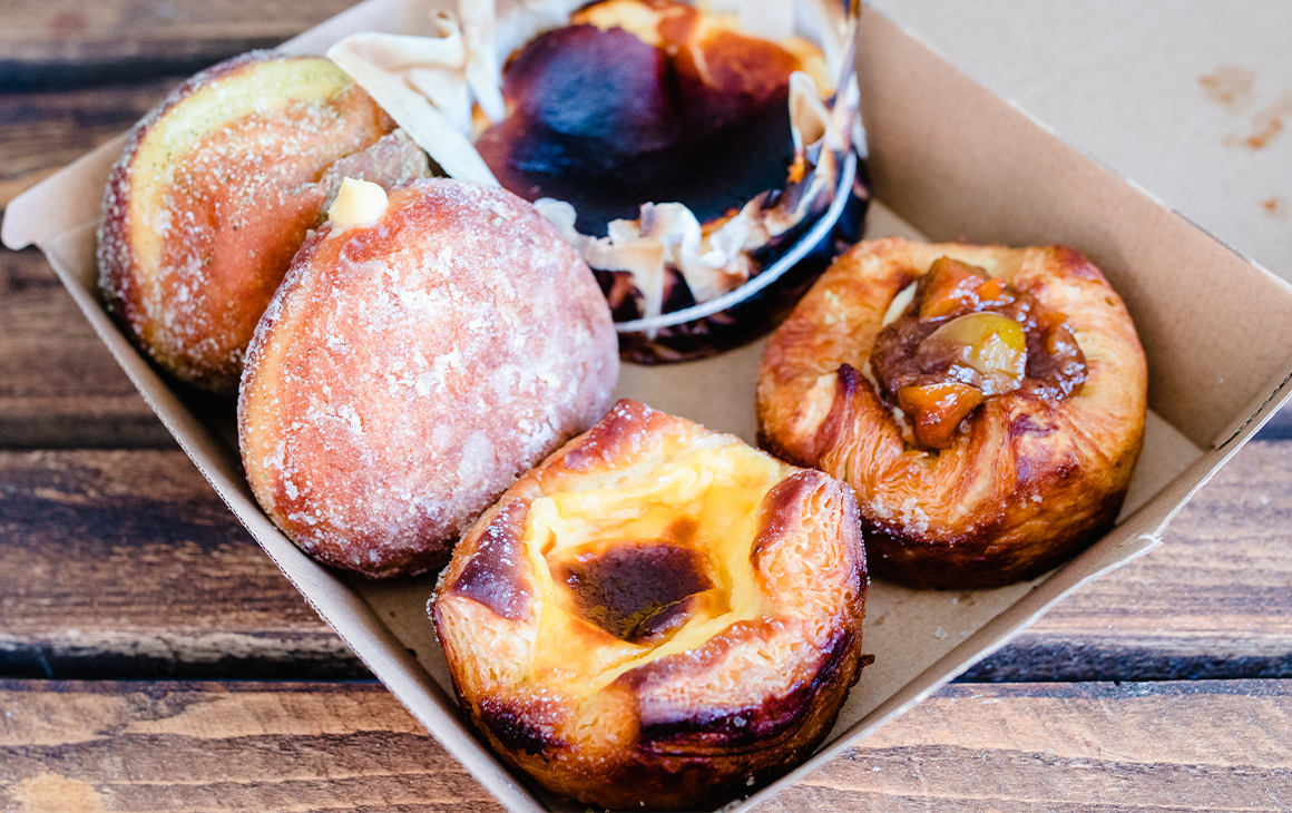 Several pastries including doughnuts, a burnt basque cheesecake and danishes in a cardboard box.