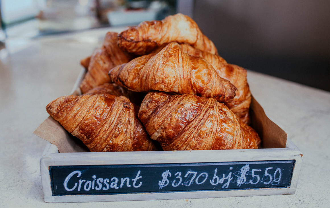 A wooden box filled with flaky golden croissants.