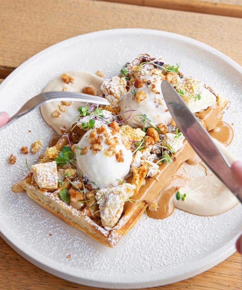 a waffle piled with ice cream and caramel sauce