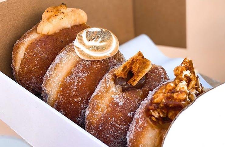 Several filled doughnuts in a cardboard box