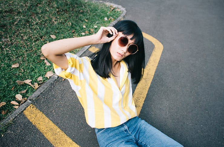 A woman wearing blue jeans and a yellow top sits on the pavement. She has a dark hair with a fringe and is wearing sunglasses.