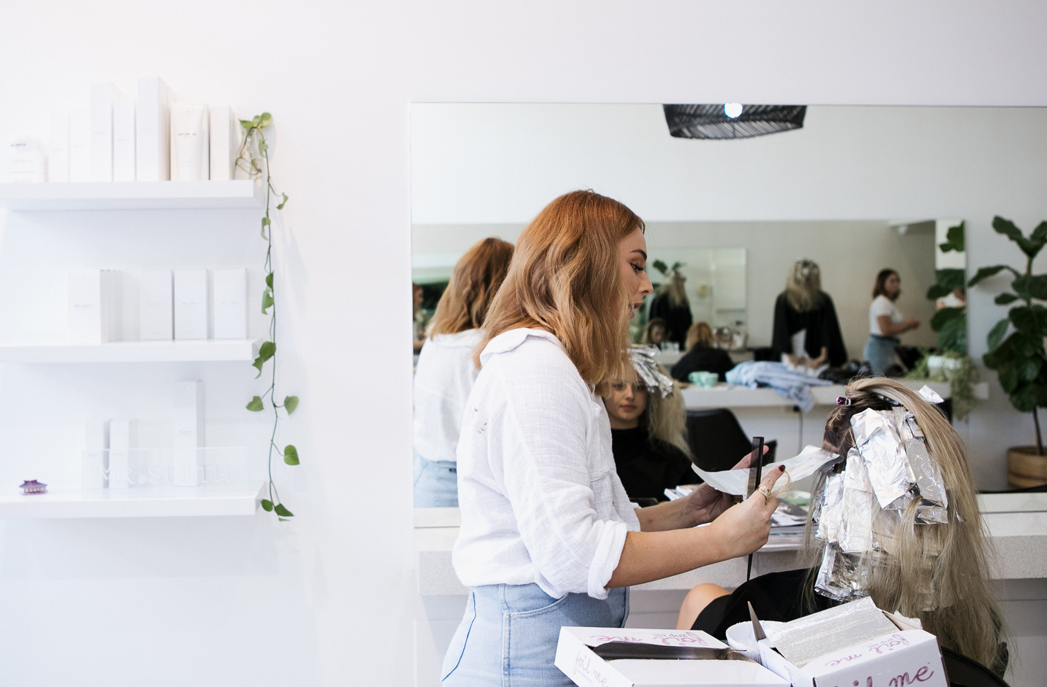 A Sunshine Coast hairdresser talks to a client while colouring her hair using foils.
