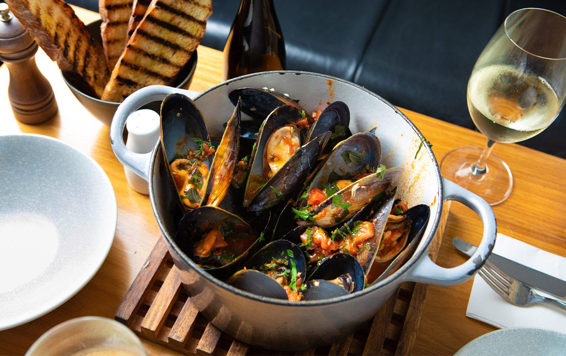 a pot of mussels with tomato sauce and a side of grilled bread