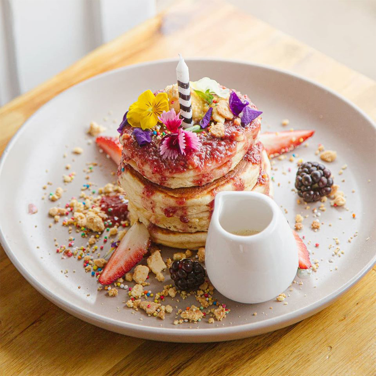 a stack of pancakes decorated to look like a birthday cake