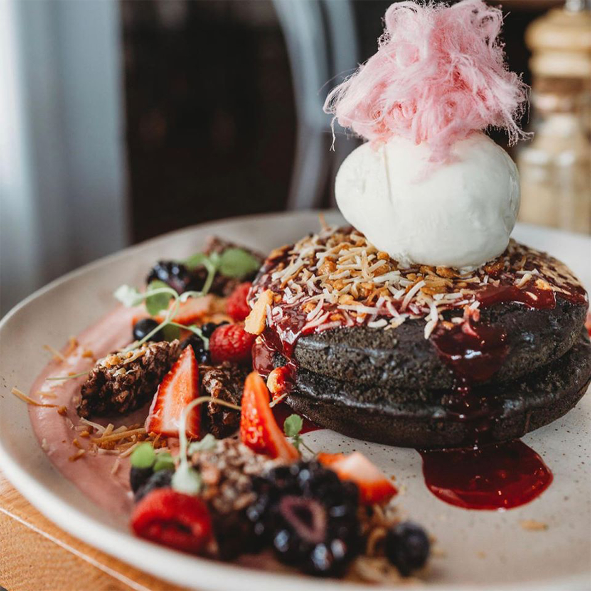 black pancakes topped with ice cream and raspberry sauce