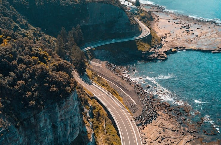 A road snakes through a stunning landscape of blue ocean and rugged cliffs.