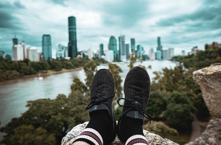 view of two feet extended out in front of a person in front of the city skyline at Kangaroo Point