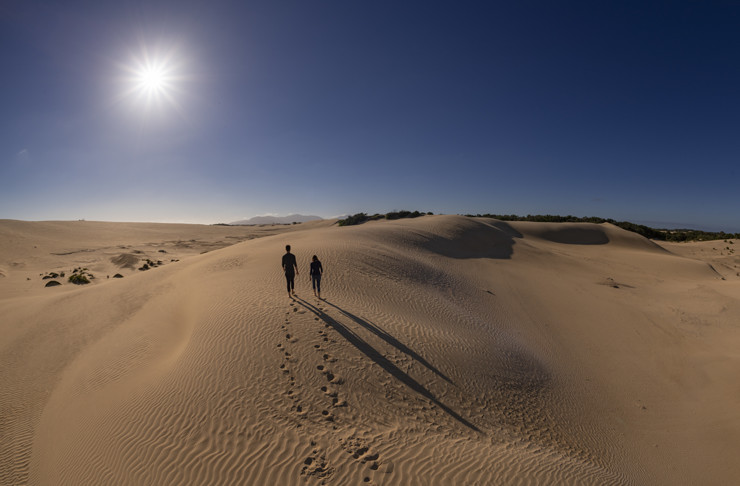 The sun shining on a hiker walking through the Big Drift sand dunes in Victoria.