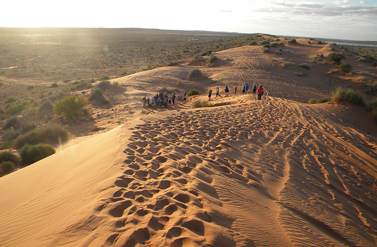 People walking across the red sands of the Big Red dunes in Western Australia.