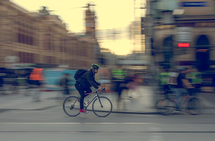 A man riding a bicycle through the intersection of Swanston Street and Flinders Street in Melbourne.