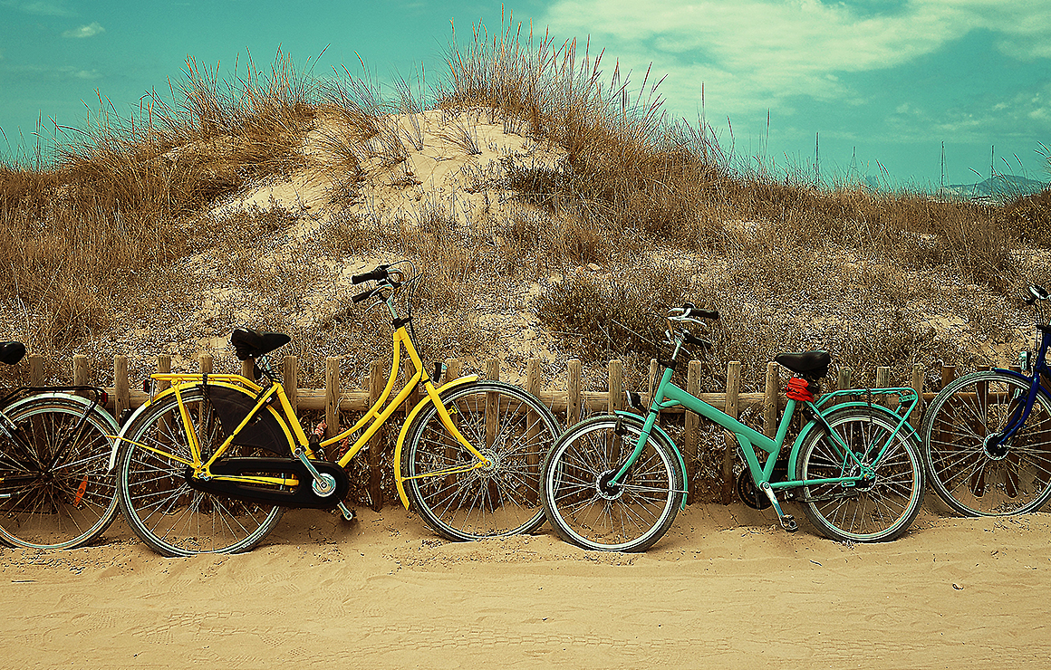 A few bikes parked next to a sand dune under a blue green sky.