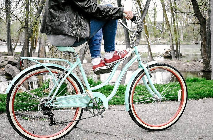 A side view of a very attractive green and red bike with the rider sitting with their feet up on the crossbar wearing red trainers and a leather jacket.