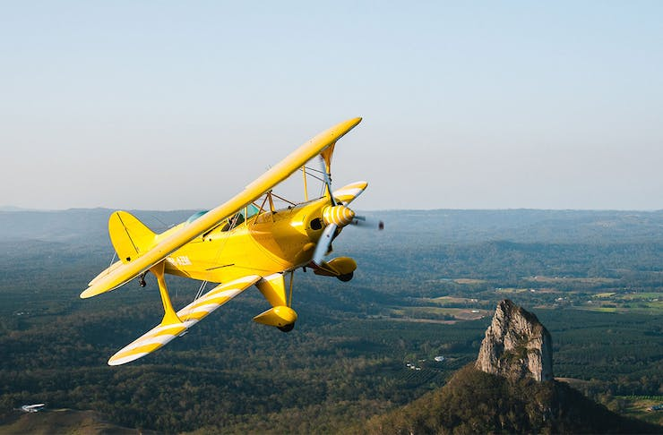 A bright yellow airplane flying over mountains
