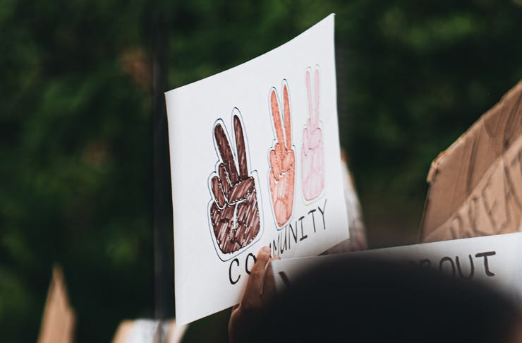 A sign being held up at a protest. The sign reads 'community' and has three different coloured hands doing a peace sign.