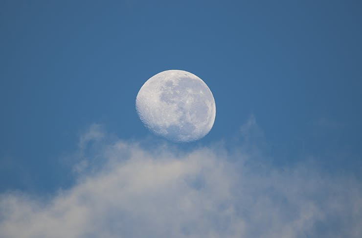 A whitish-blue moon in the mostly clear early evening sky.