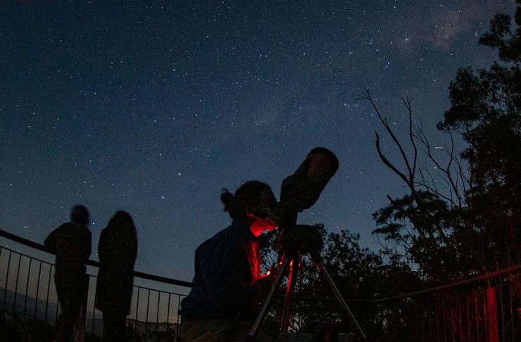 A person peering through a telescope on a starry night.
