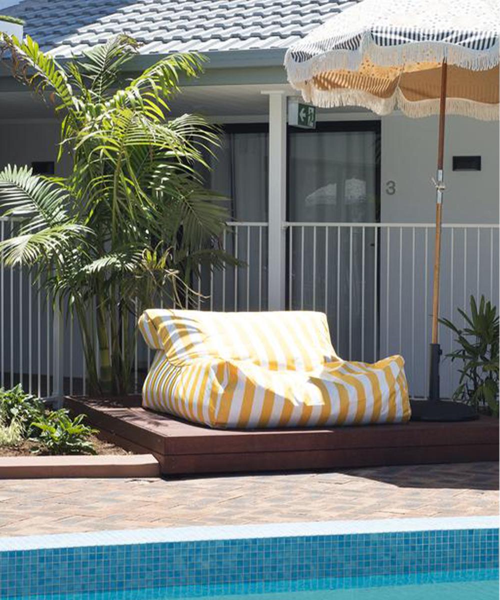 a pool cushion under an umbrella by a pool
