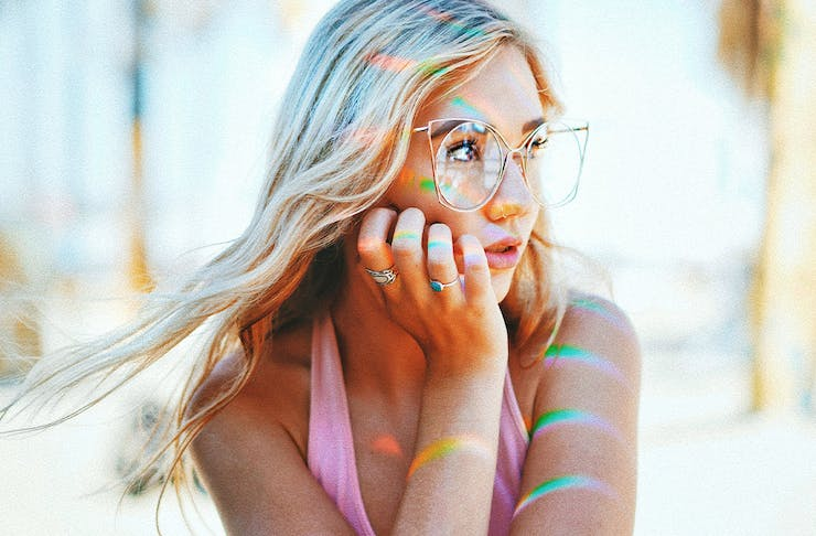 Woman looking into the distance with coloured lights on her