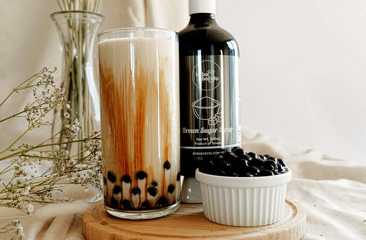 a glass of bubble tea next to a bottle of syrup and a cup of pearls