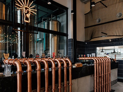 the interior of a brewpub, with copper beer taps
