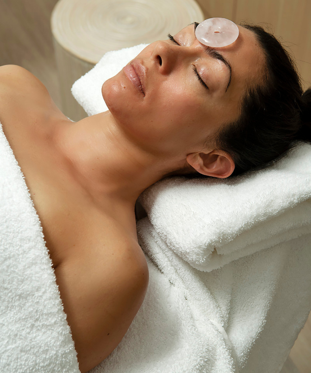 guest lays on massage table with rose quartz stone on forehead