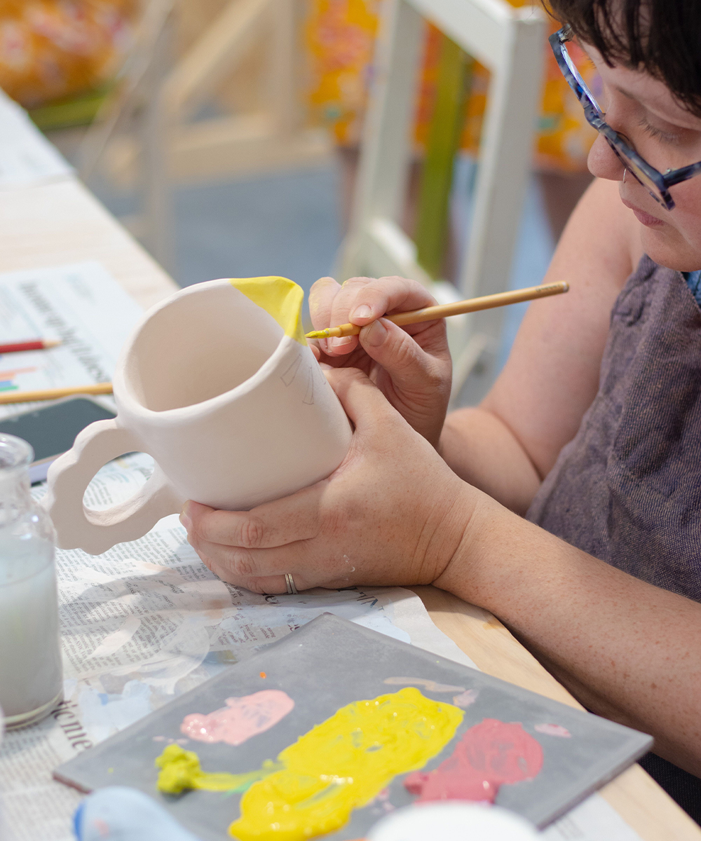a person painting a clay jug