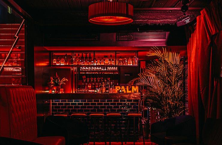 An underground speakeasy bar wrapped in red velvet.