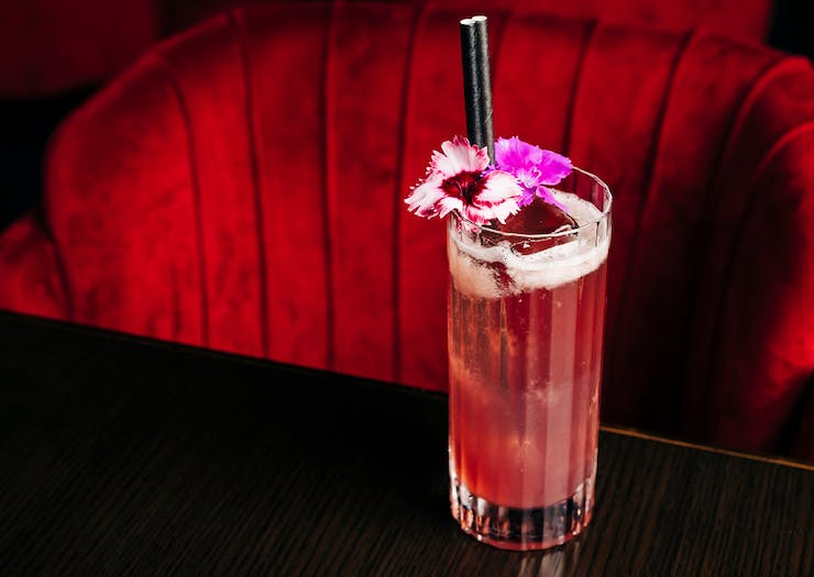 a pink cocktail on a table in front of a plush red chair