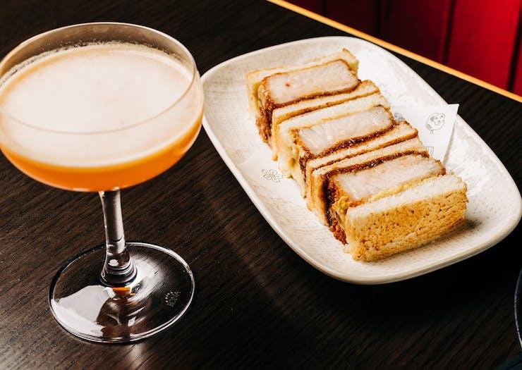 a cocktail beside a plate of pork katsu sandos