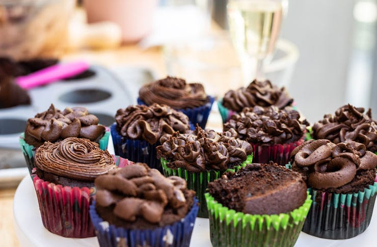 Chocolate cupcakes with a glass of champagne in the background.