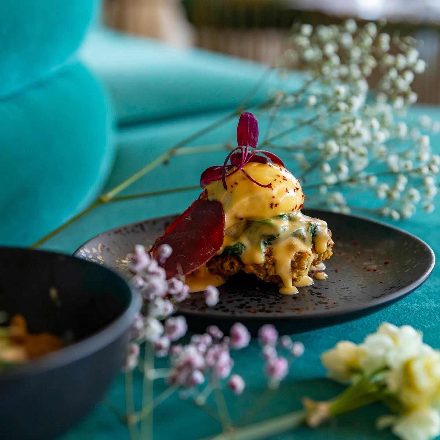 A close-up shot of a colourful brunch egg-dish, garnished with purple flowers and dripping with Hollandaise sauce.