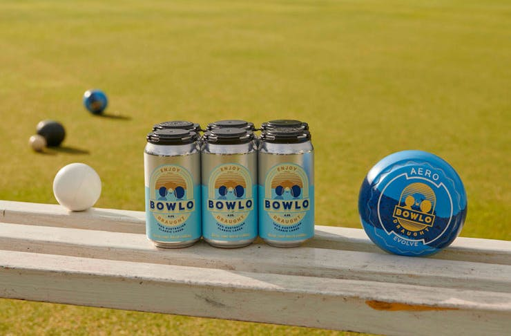 A six-pack of Bowlo Draught with a bowling green in the background.