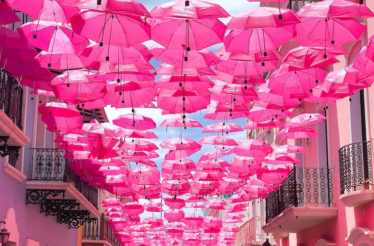 Pink umbrellas fill the rooftop over some sunny street in the med somewhere.