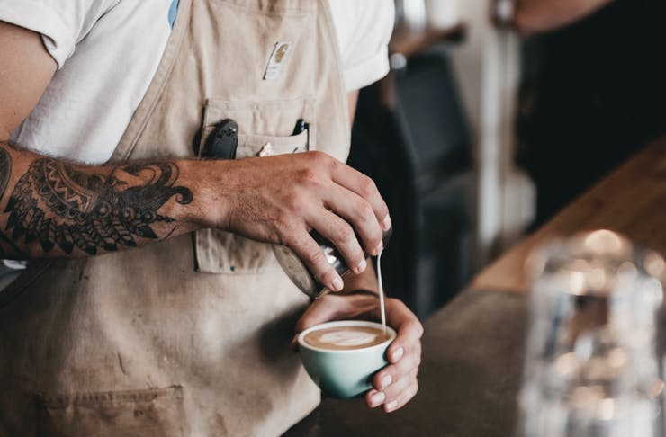 A barista brews a perfect coffee in a cafe.