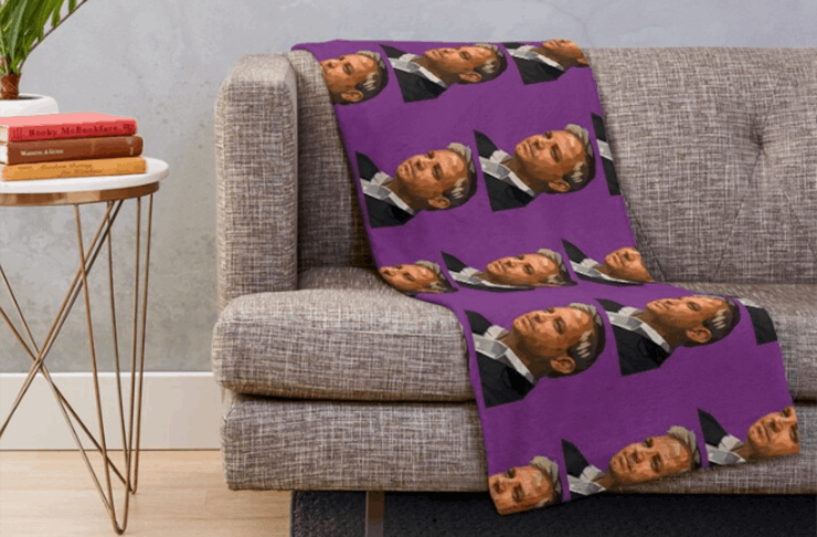 A throw rug laying on a couch with Prof. Brett Sutton's face on it.