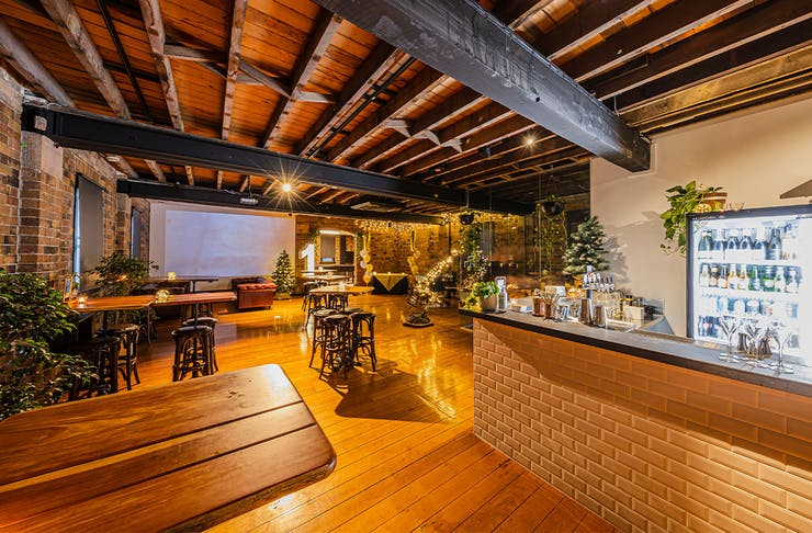 an indusrial-style function room wit wooden floors and a tiled bar