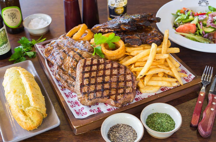 a plate of ribs, steak, chips and sides