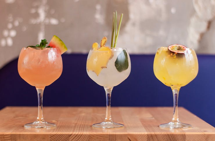 Three gin cocktails lined up on a table